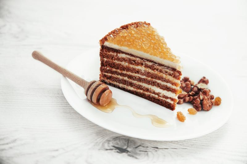 Honey cake with golden pearls and mint leaf and cinnamon on stone plate isolated stock photography
