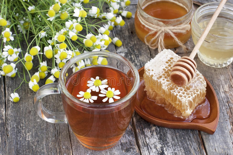 Honey, camomile and tea on wooden background. Glass cans full of honey on wooden table stock image