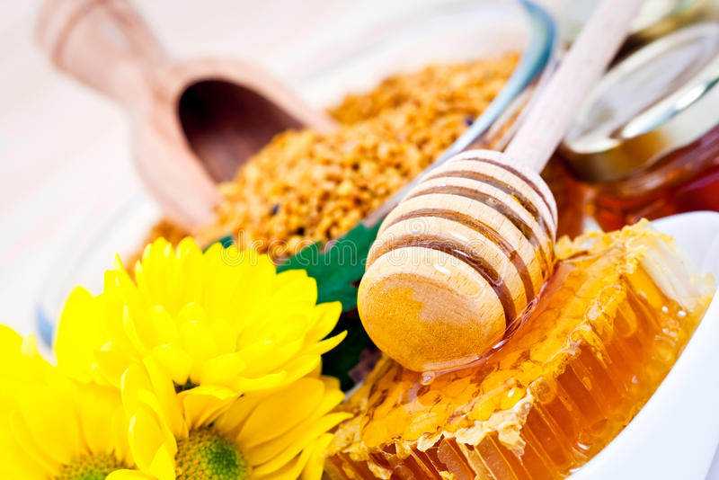 Honey and cereals. A wooden honey dipper on honeycomb with yellow flowers and cereals for breakfast in the background royalty free stock photos