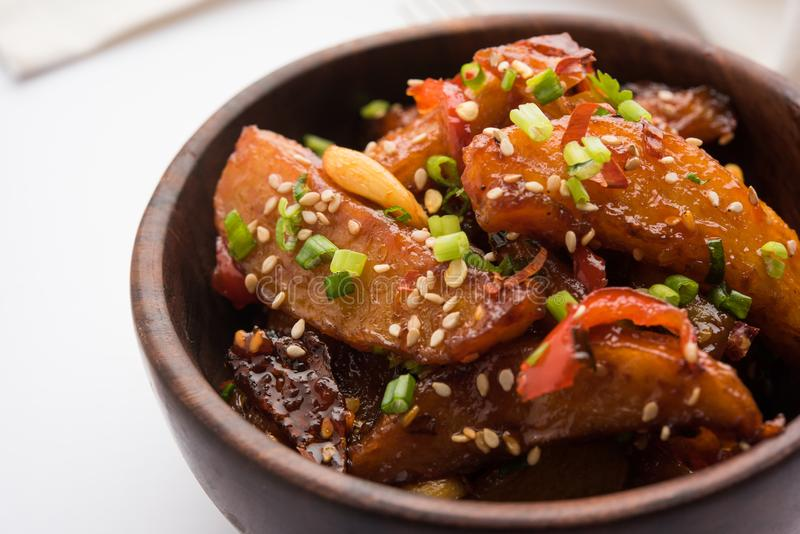 Honey chilli potato or Potato wedges. Popular Indian-Chinese starter recipe, garnished with sesame and onion. selective focus royalty free stock photos