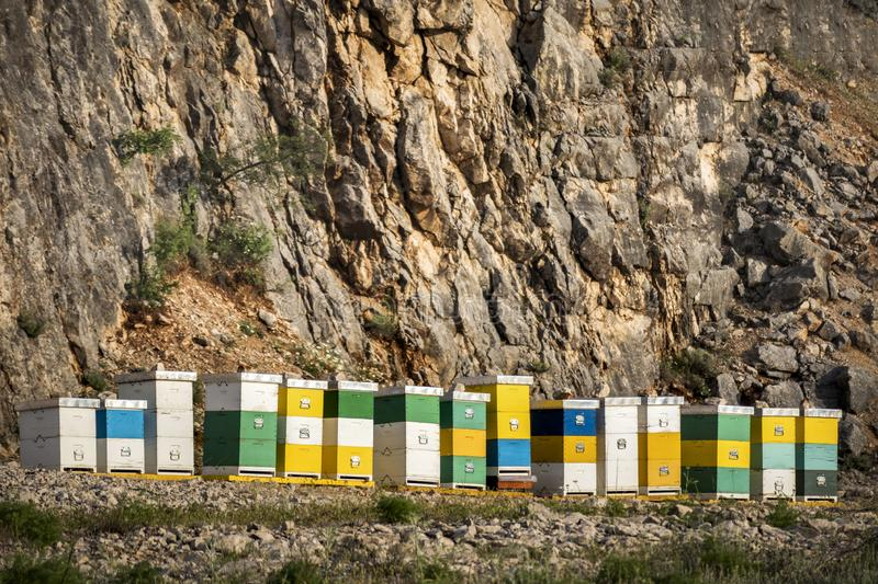 Abandoned quarry with colorful boxes. Honey colorful beehives in a row in nature on the island Brac in Croatia royalty free stock images
