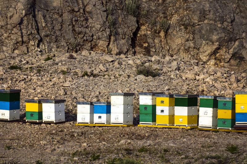 Abandoned quarry with colorful boxes. Honey colorful beehives in a row in nature on the island Brac in Croatia royalty free stock image