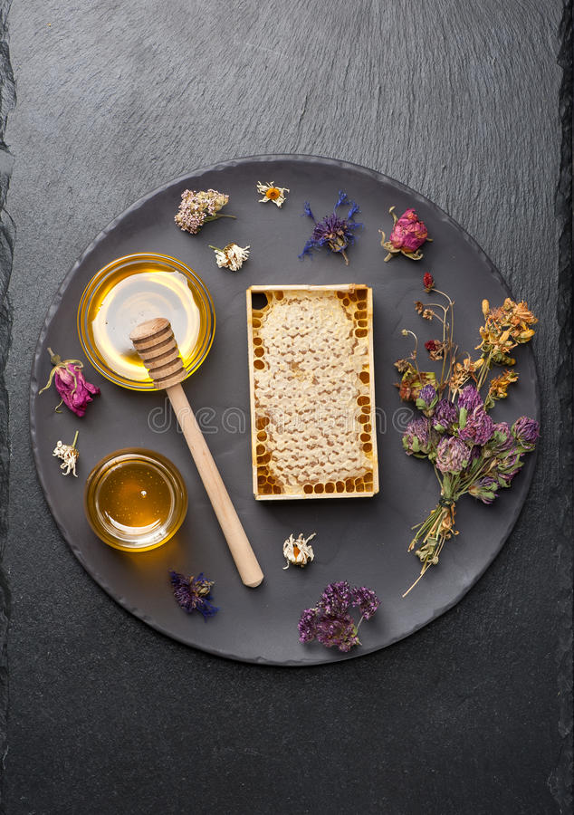Honey comb and dried herbs. Honey jar, honeycomb and dried herbs stock images