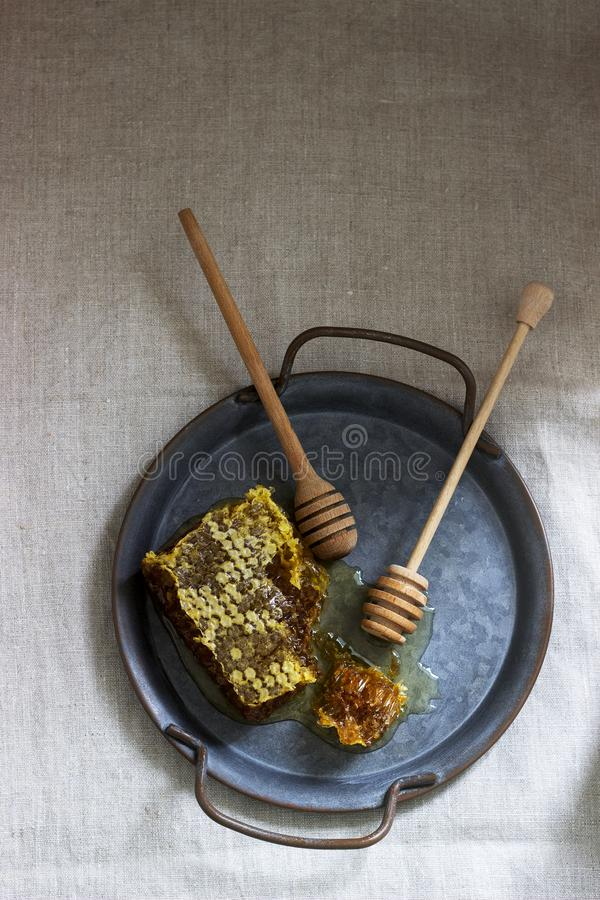 Honey comb on a tin tray on linen tablecloths. Rustic style. Honey comb on a tin tray on linen tablecloths. Rustic style, selective focus royalty free stock photo