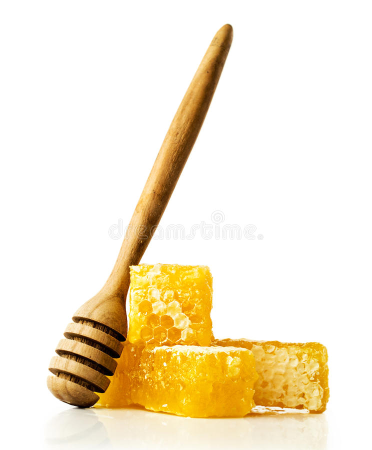 Honey comb with a wooden dipper. Isolated on white royalty free stock photo