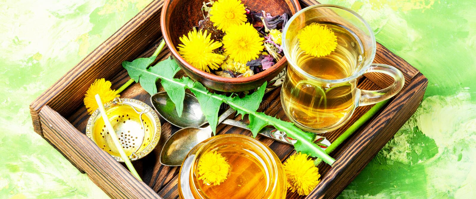 Honey from dandelion and tea. Honey from a blooming spring dandelion and cup of tea royalty free stock photography