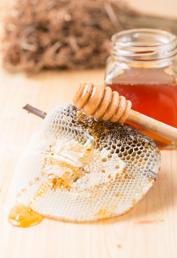 Honey dipper on the bee honeycomb. On wooden background stock photos