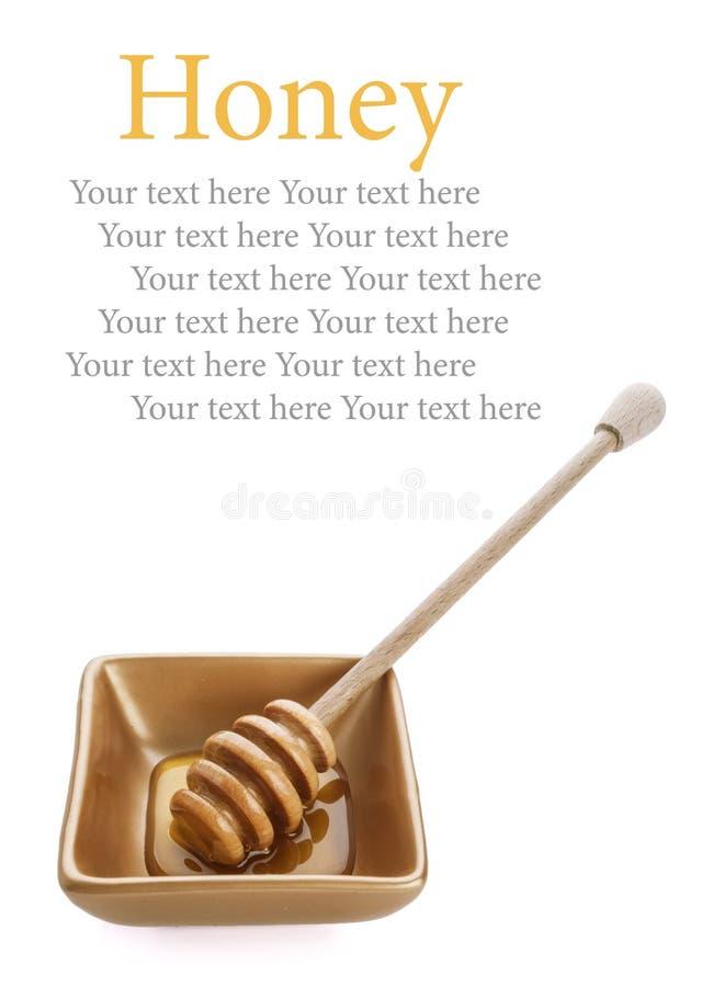 Honey dipper with honey in golden bowl on white background stock image