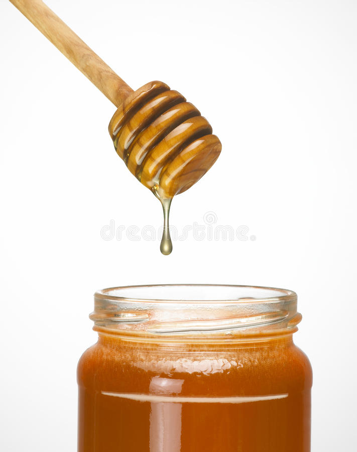 Honey dripper with jar. On white background stock photo