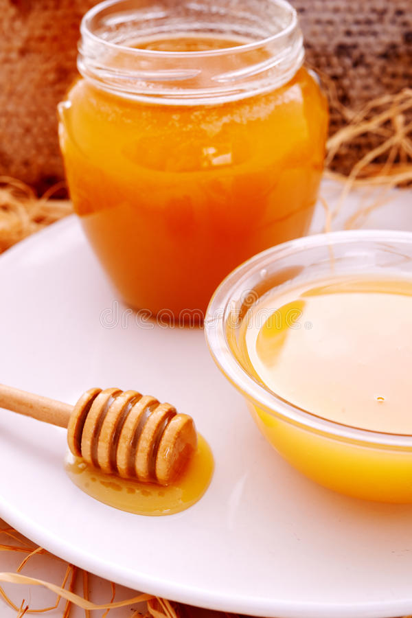 Honey dripper and jar of honey. And honeycomb as background stock image