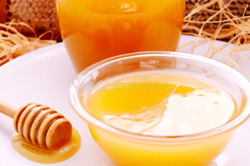 Honey dripper and jar of honey. And honeycomb as background stock images