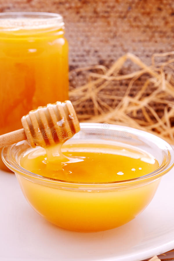 Honey dripper and jar of honey. And honeycomb as background royalty free stock image