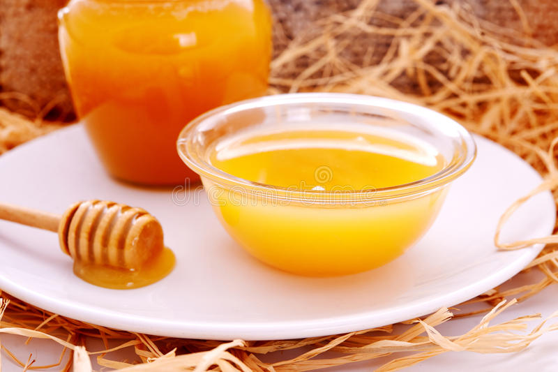 Honey dripper and jar of honey. And honeycomb as background royalty free stock photo