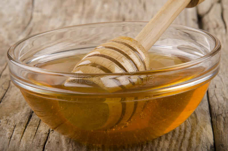 Honey and dripper in a small glass bowl. Bee honey and dripper in a small glass bowl stock image