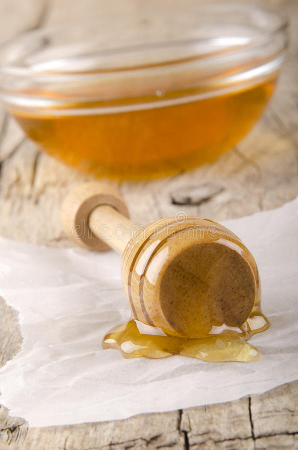 Honey dripper with some bee honey. On kitchen paper stock photos