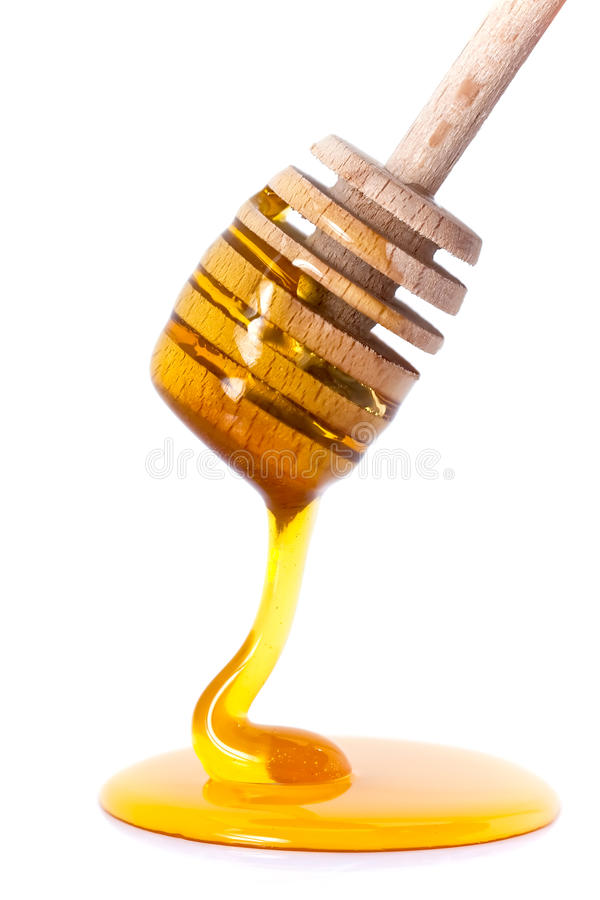 Honey dripping from dipper stock image