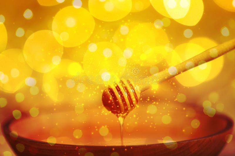 Honey dripping from dipper into bowl against blurred lights royalty free stock photography