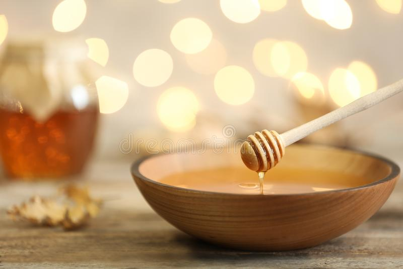Honey dripping from dipper into bowl on table against blurred lights. Space for text stock photo