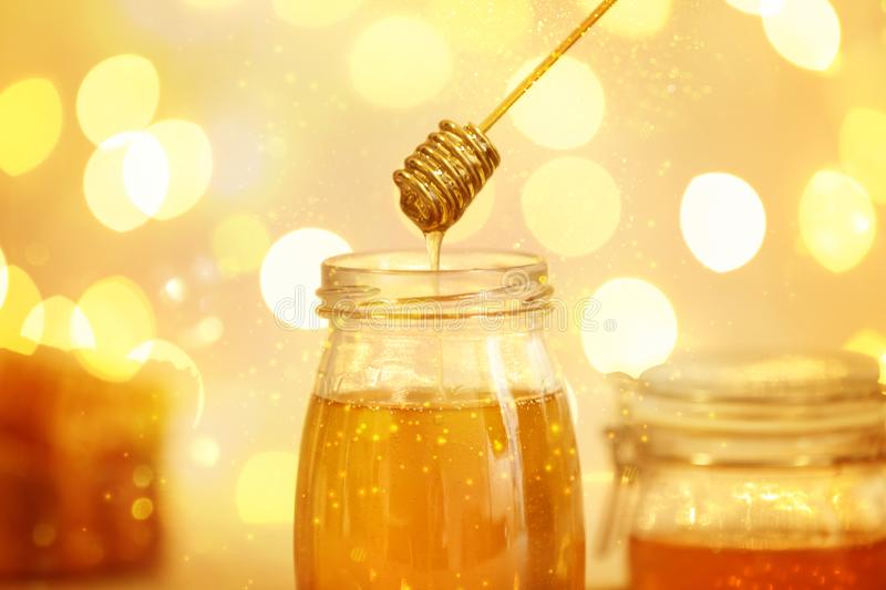 Honey dripping from dipper into jar against blurred lights royalty free stock image