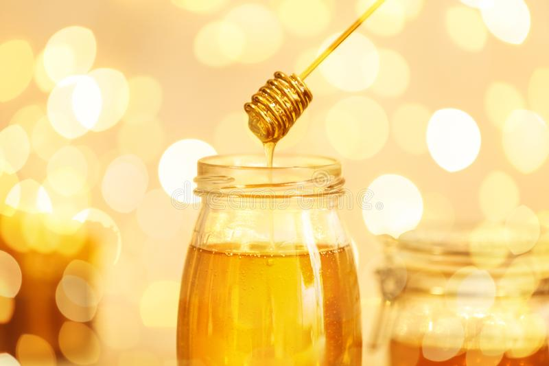 Honey dripping from dipper into jar against blurred lights royalty free stock photography