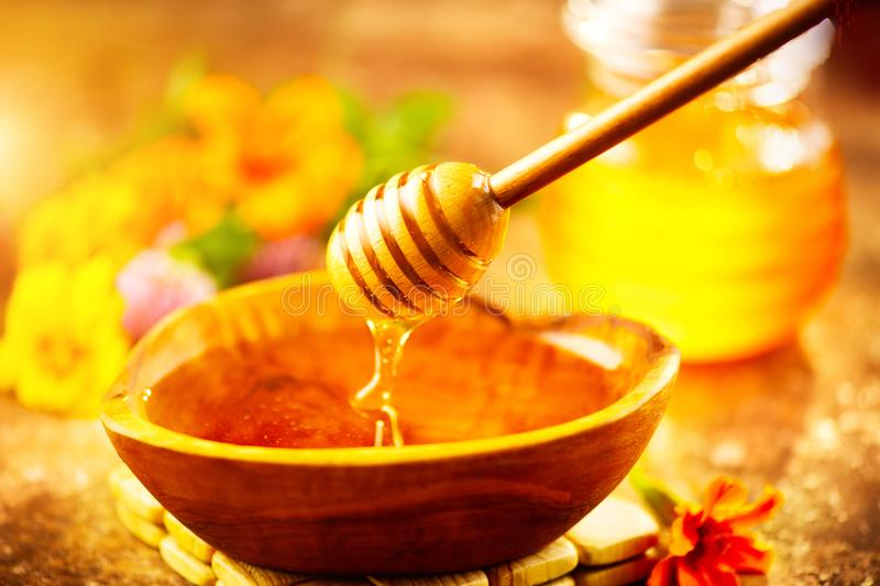 Honey dripping from honey dipper in wooden bowl. Healthy organic thick honey pouring from the wooden honey spoon royalty free stock photography
