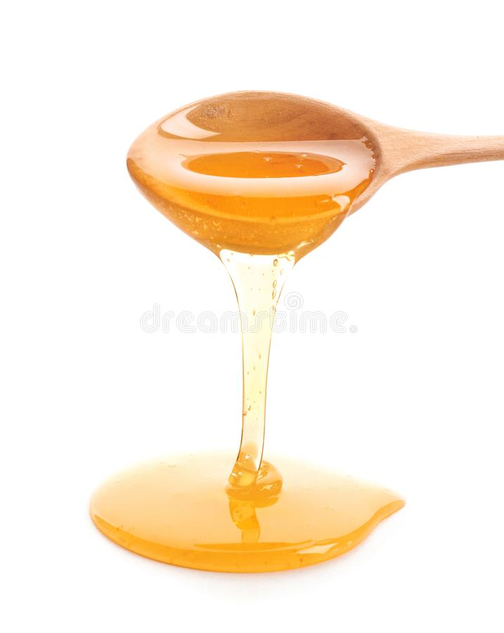 Honey dripping from spoon. On white background stock photos
