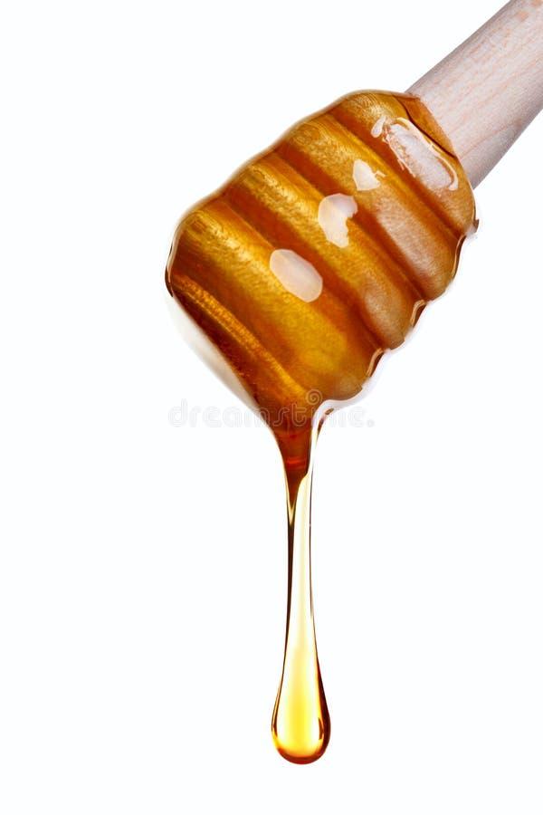 Honey dripping from a wooden dipper