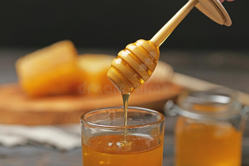 Honey dripping from wooden dipper into glass stock photo