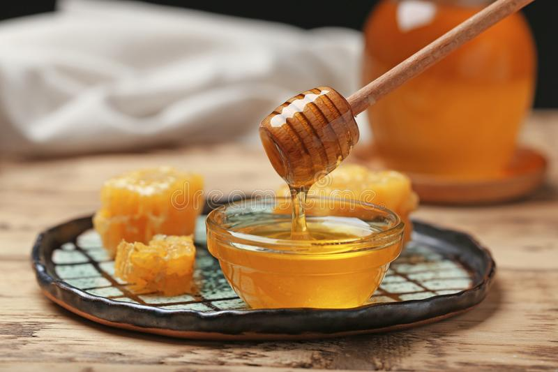Honey dripping from wooden dipper into glass bowl stock photos