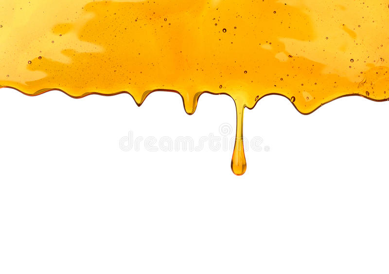 Honey dripping from a wooden dipper stock photography