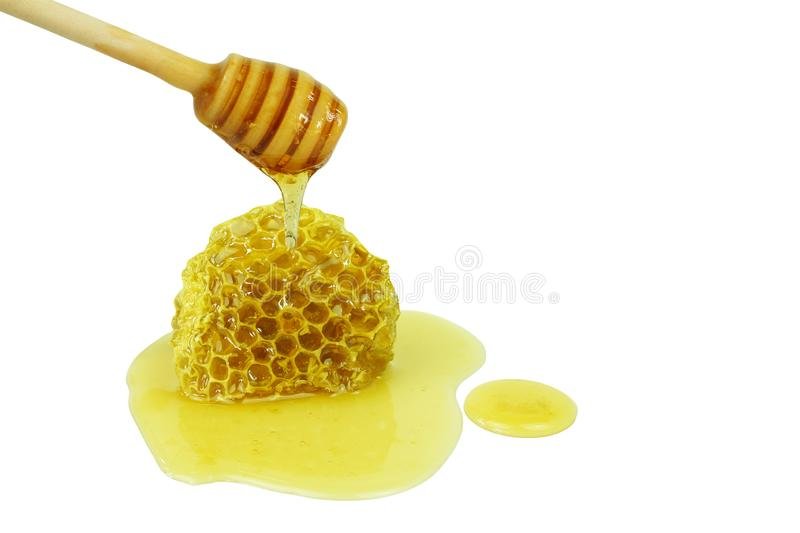 Honey dripping on wooden dipper pouring on honeycomb isolated on a white background, concept of bee products stock photos