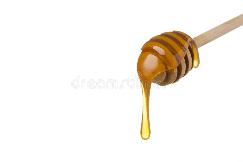 Honey dripping from wooden honey spoon royalty free stock image