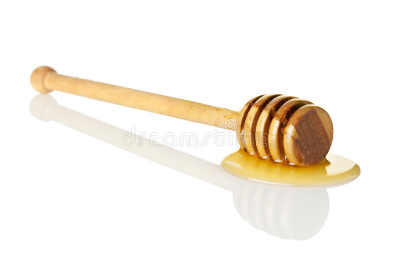 Honey drizzler. Wooden honey drizzler in small puddle isolated on white background royalty free stock photos