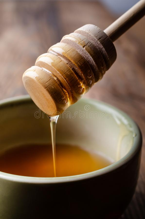 Honey Drizzler Flowing into Green Bowl on Woodem Table stock photos