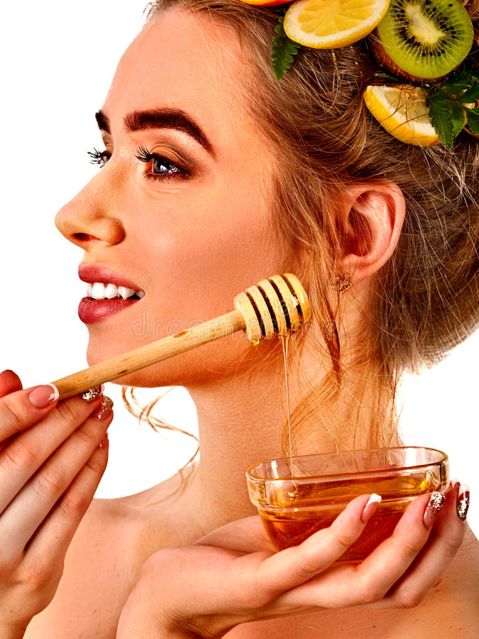Honey facial mask with fresh fruits for hair and skin on woman head. Girl face hold honeycombs for homemade organic skin and hair therapy. Medical properties stock images