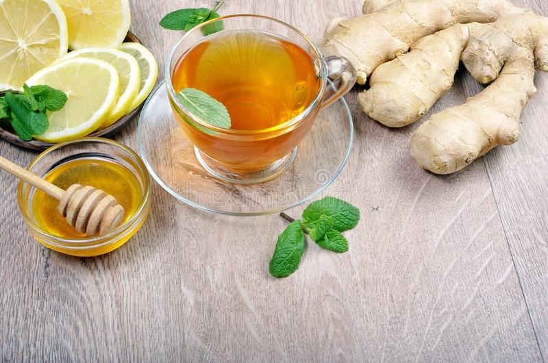 Honey, ginger, lemon and cup of tea on the wooden table. cold and flu remedy. close up. royalty free stock photos