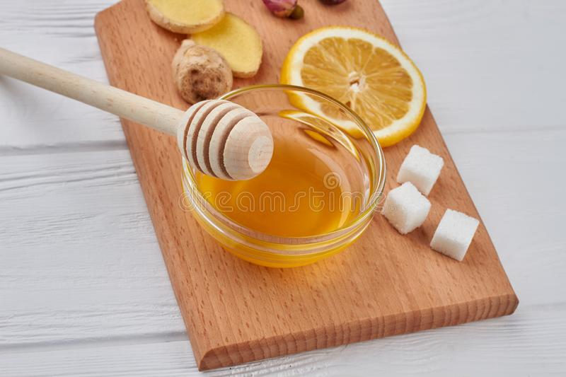 Honey with ginger and lemon on the cutting board. Best natural cold and flu recipe royalty free stock images