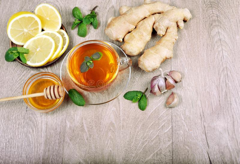 Honey, ginger, lemon, garlic and a cup of tea on a wooden table. for cold and flu. top view. stock photos