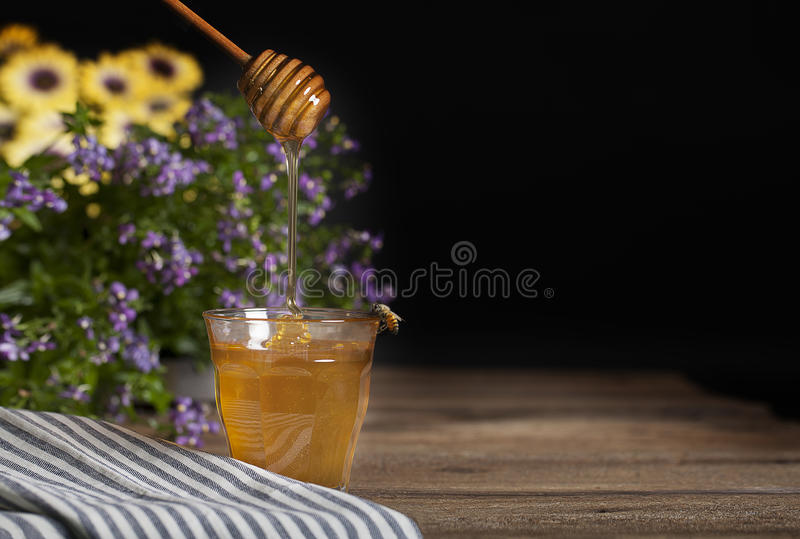 Honey in Glass with Bee. A wooden honey dripper filling a glass with honey, honey bee perched on side of glass, yellow and purple flowers in background royalty free stock photo