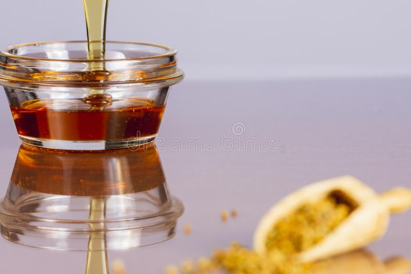 Honey in glass bowl with wooden scoop with pollen grain in blur on white background, copy space image. Close up of honey in glass bowl with wooden scoop with stock photos