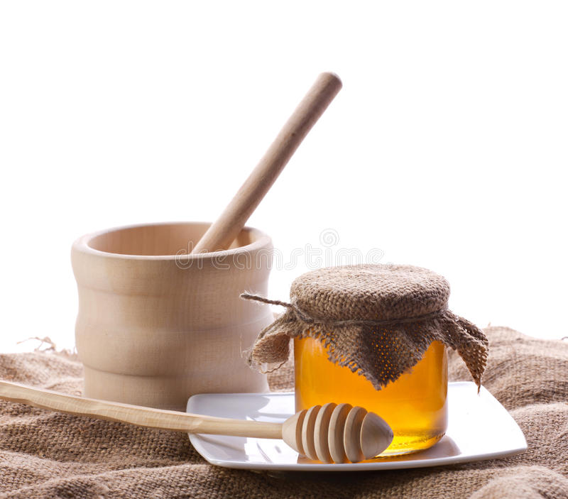 Honey in glass with drizzler. Translucent honey in glass with drizzler on plate and wooden jar standing on sacking mat, on white background royalty free stock image