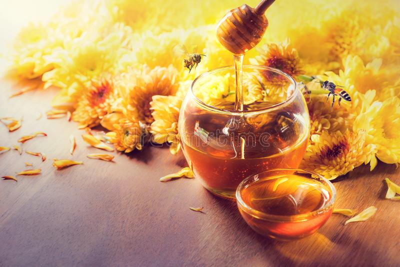 Honey in glass jar with bee flying and flowers on a wooden floor.  stock images