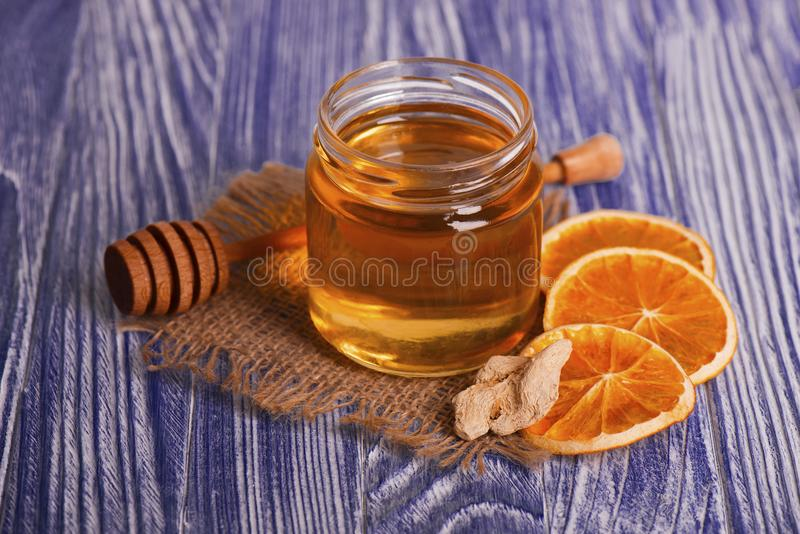 Honey in glass jar, ginger and dry slices of orange on vintage wooden background. Aromatic spices. royalty free stock image