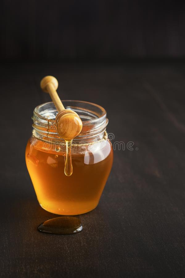 Honey in a glass jar with honey dipper on rustic wooden table background. royalty free stock photography