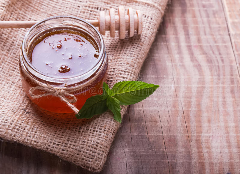 Honey in a glass jar, honey spoon and mint leaves on the wooden. Table close-up stock image