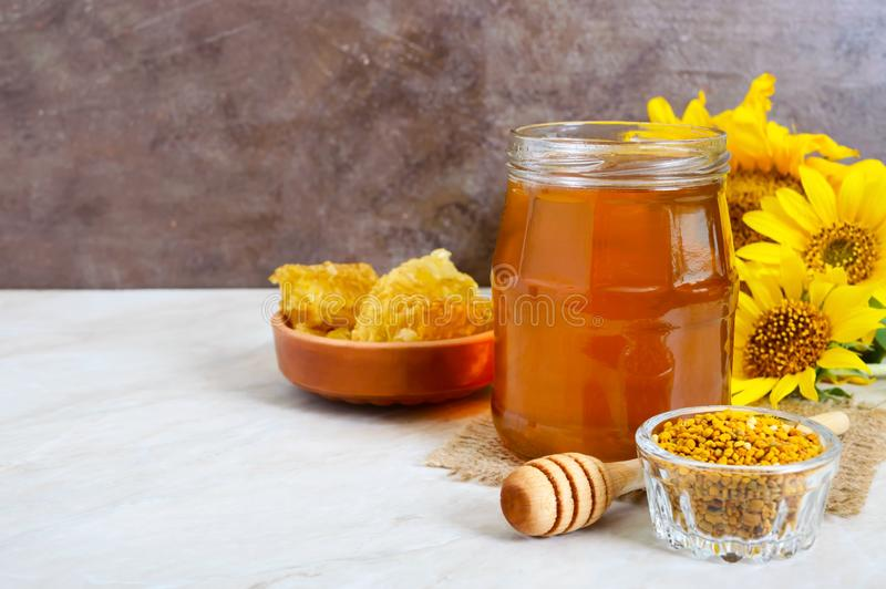 Honey in a glass jar, honeycomb, pollen. Products of beekeeping. royalty free stock photography