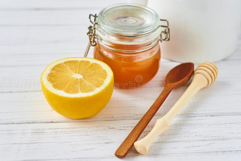 Honey in glass jar and lemon on a white background close up royalty free stock photos