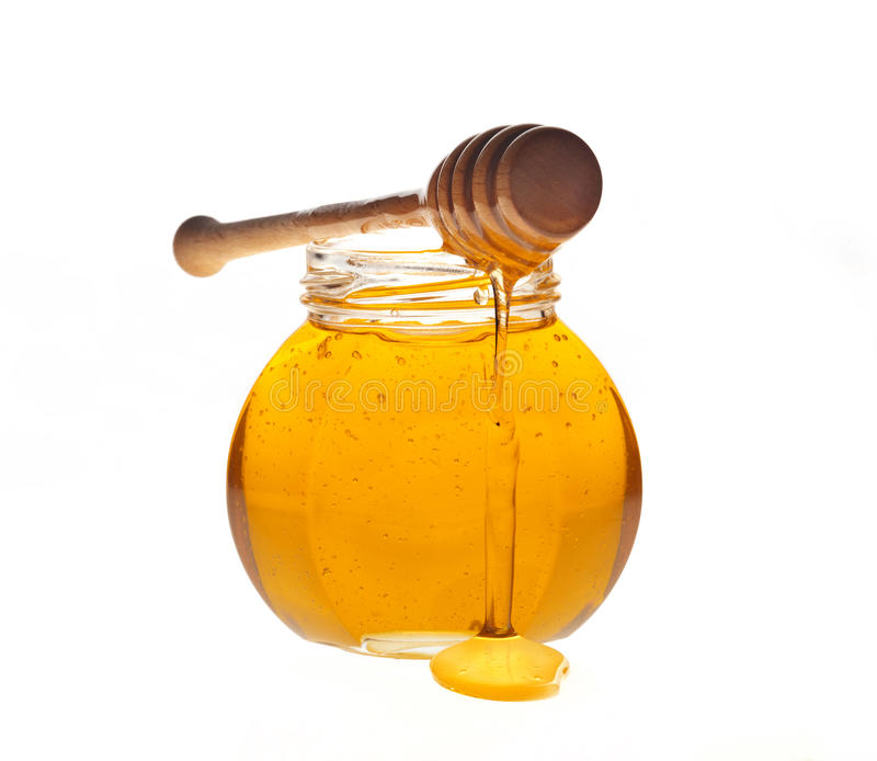Honey. Glass jar of honey with wooden drizzler on a white background stock photos