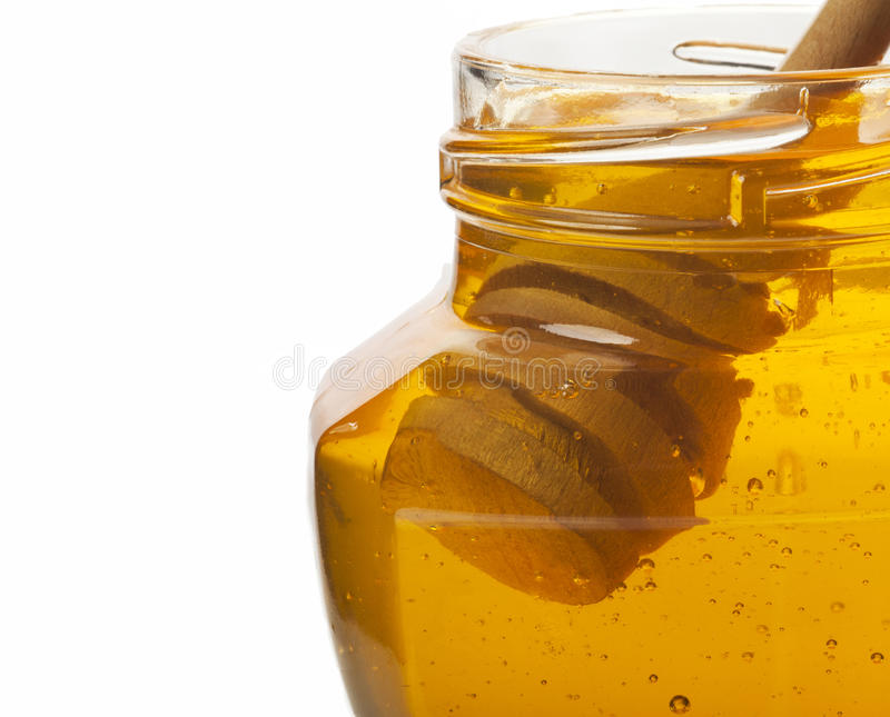 Honey. Glass jar of honey with wooden drizzler on a white background with copy space royalty free stock photography