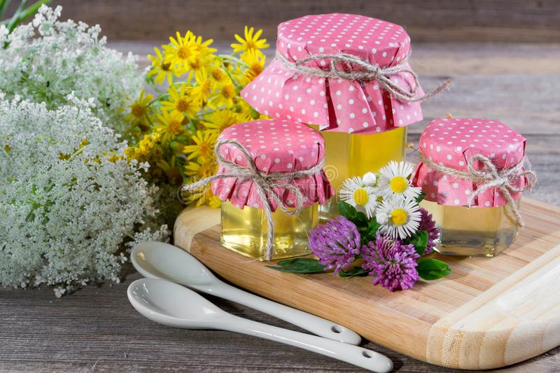 Honey in a glass jars, and honey dipper with wild flowers stock image